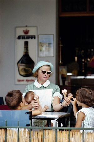 A childminder hands out ice creams to her charges at a cafe, Italy, August 1967