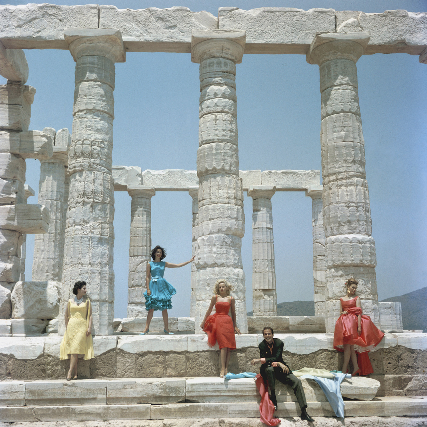 Dimitris Kritsas: Dimitris Kritsas, a fashionable young couturier, poses among the gleaming Doric columns of the temple to Poseidon at Sounion, 1961