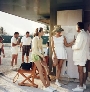 Tennis in the Bahamas: Two women stand talking to a man on the edge of a tennis court in the Bahamas, c. 1957